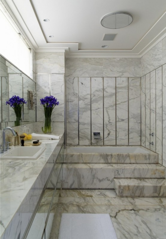 a gorgeous neutral marble bathroom with a floating vanity, a sink and a mirror plus a large bathing space