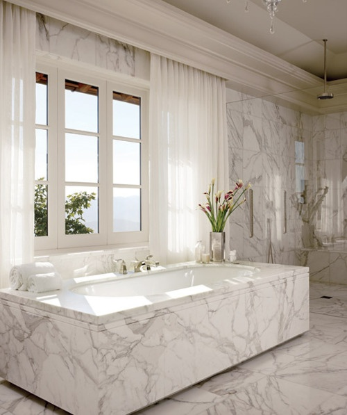 a luxurious white marble bathroom with a large window with curtains, a tub clad with marble and a shower space