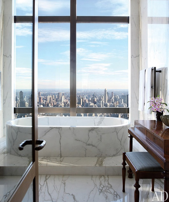 a fantastic bathroom with dark stained furniture and a tub clad with white marble plus a gorgeous and breathtaking view