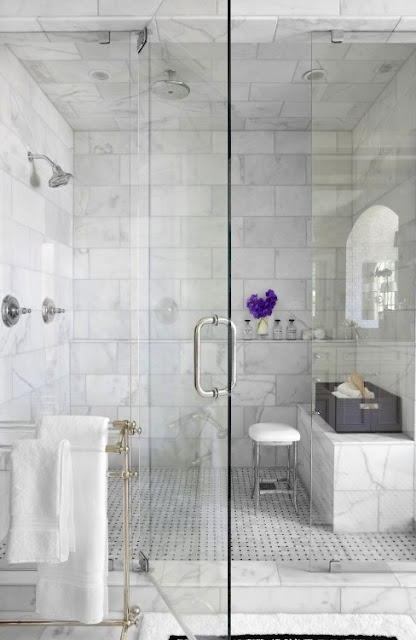 an elegant bathroom done with white marble tiles and a matching tile floor plus a marble bench in the shower space