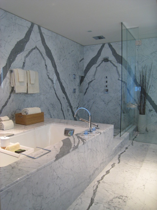 a modern bathroom with grey marble, a bathtub, a shower space looks chic and bold