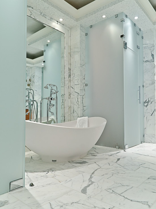 a chic bathroom all done with white marble, a mirror wall and touches of blue frosted glass