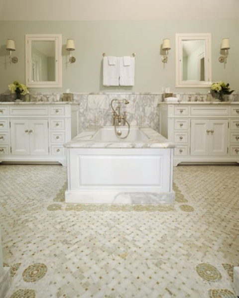 a vintage-inspired white bathroom with white vanities and a tile floor and a sink zone with white marble plus a tub clad with it, too