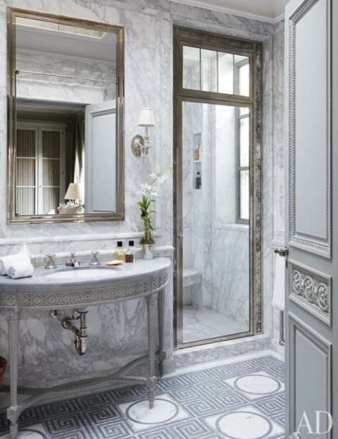 a luxurious Greece-inspired bathroom with white marble, metallic touches and patterns