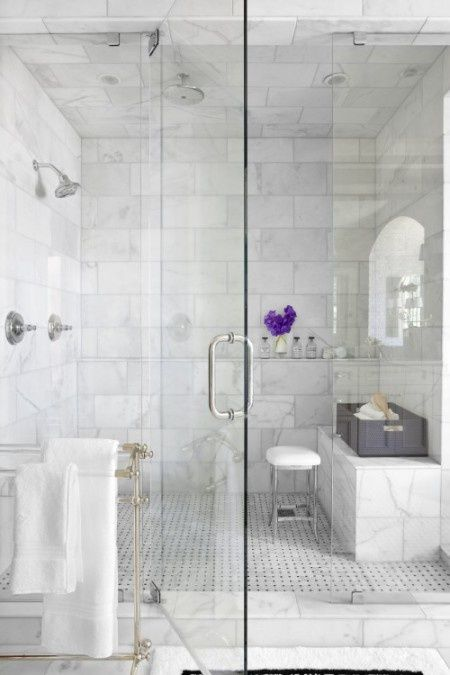 a chic shower space done with marble tiles and matching patterned tiles on the floor plus seamless glass doors