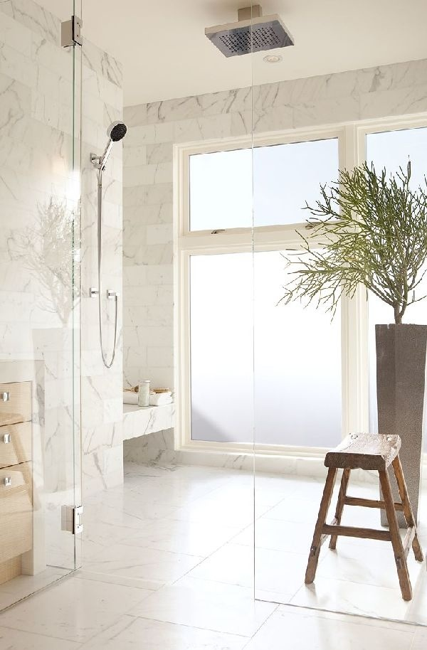 a neutral and welcoming shower space with a frosted glass window and white marble tiles all over