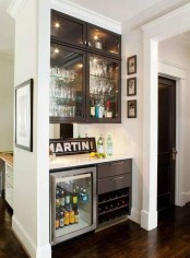 a stylish home bar with several cabinets, a fridge and a mirror backsplash plus a sign is a cool idea