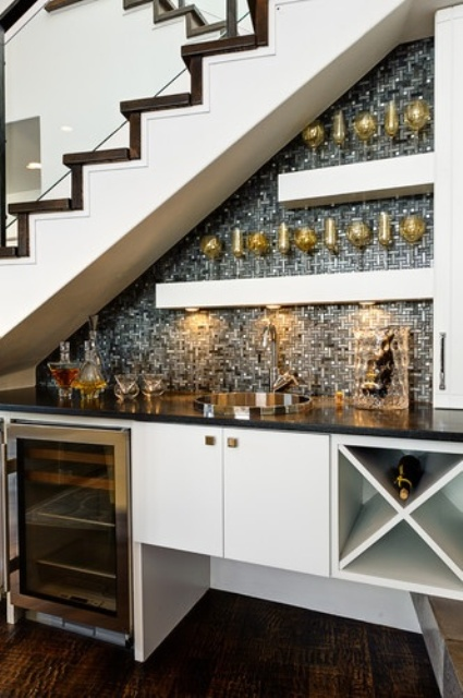 an open under the stairs home bar with a mosaic silver tile backsplash, open shelves and a fridge plus a cabinet and built-in lights