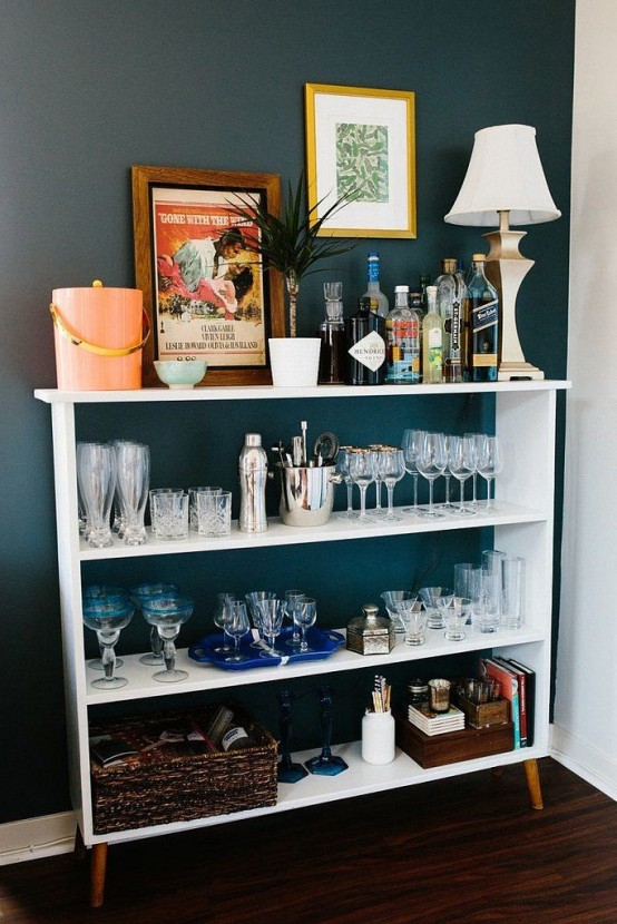 an open home bar made of a dresser with lots of glasses, bottles and other stuff you may need plus a lamp