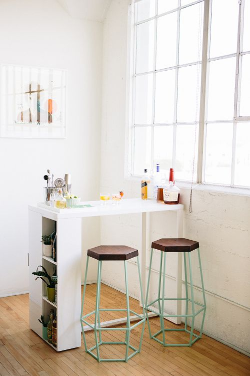 a white mini bar with a space to sit, with a closed storage compartment and some things on the table and mint stools
