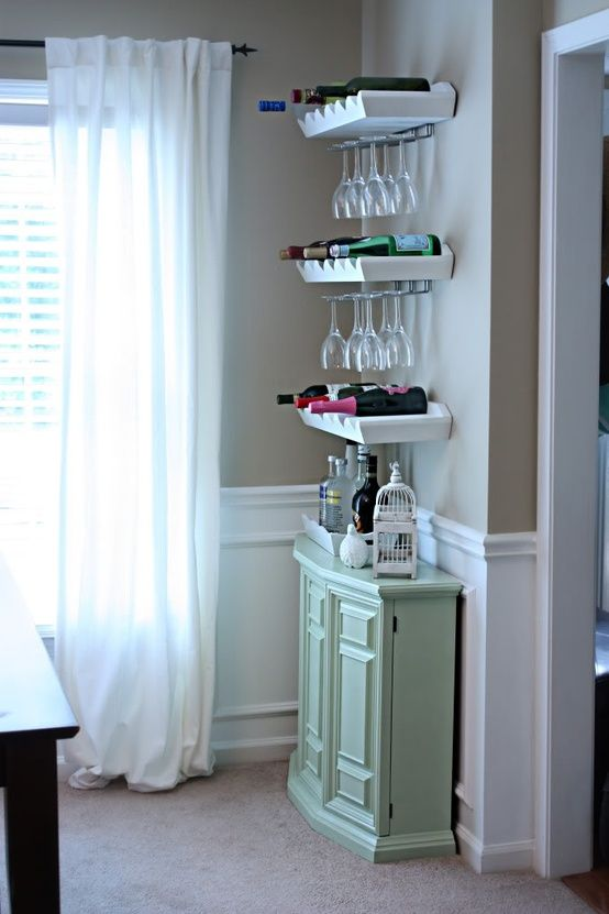 a small mint-colored bar, open shelves for holding bottles and glasses form a cool home bar that doesn't take much space