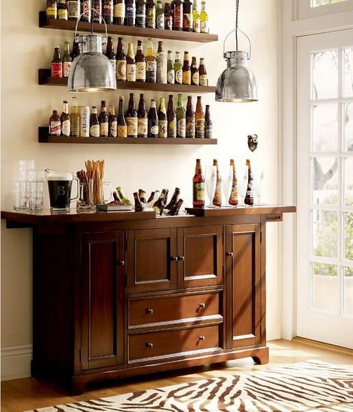 a vintage wooden bar and matching shelves over it to organize a whole home bar in the space