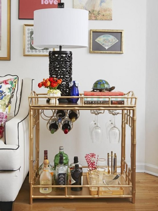 a chic gold bar cart with bottle and glass holders, with a gold tray and gold edge glasses