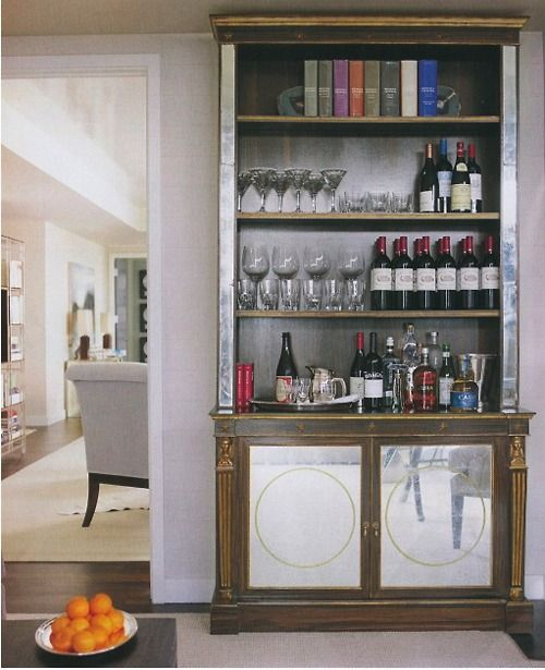 a vintage bookcase transformed into a chic home bar with glasses, bottles and everything else necessary in the cabinet part