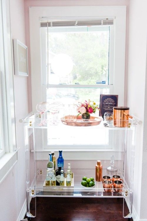 a modern home bar of clear acryl, with bright blooms and copper barware plus pink glasses for a chic and fresh look