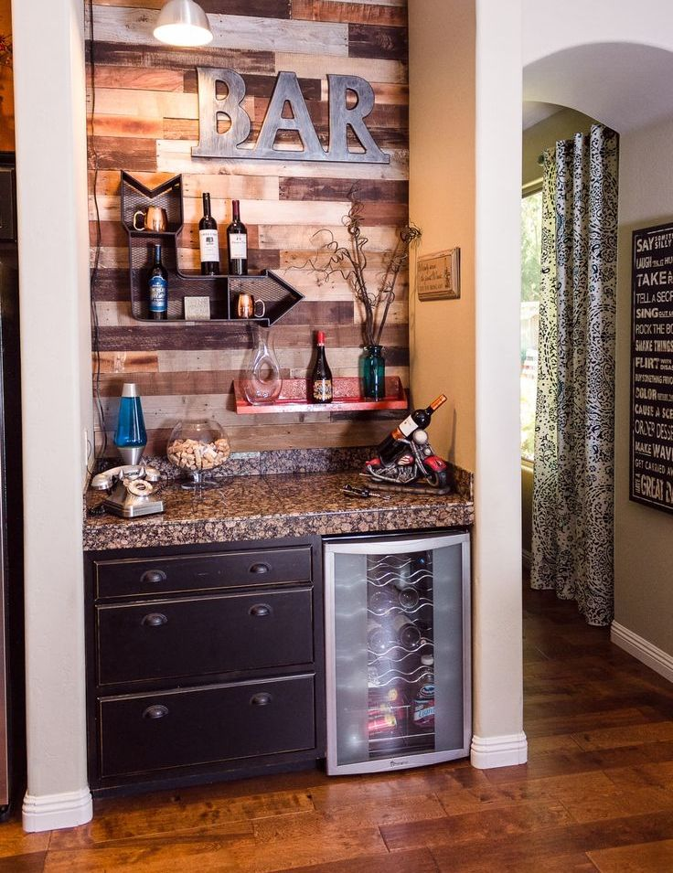 a small rustic home bar with a wood clad wall, open shelves, a cabinet and a fridge plus built in lights