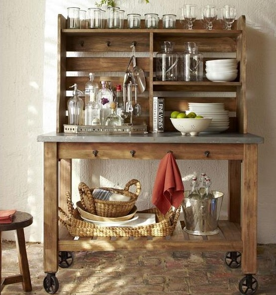 a rustic home bar made of wood and concrete, with glasses, bottles and baskets for storage