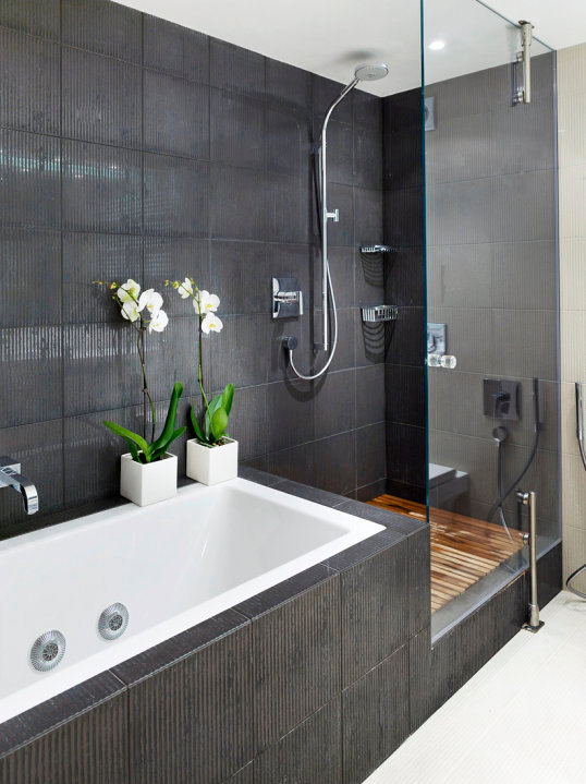 Luxury-modern-bathroom-design-with-shower-cabin-and-tiles-on-walls-wooden-floor-bathtub-and-decorations
