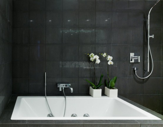 Modern-bathroom-design-with-luxury-porcelain-bathtub-modern-shower-area-and-tiles-on-walls