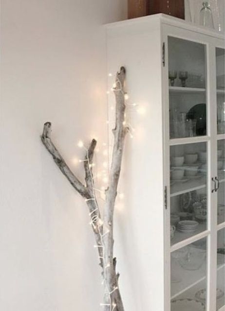 branches wrapped with lights are a nice Christmas tree alternative that can be used in any space