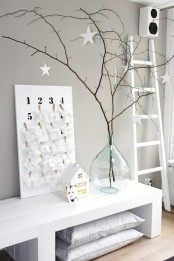 simple branches with white paper stars placed into a large bottle as an alternative minimalist Christmas tree