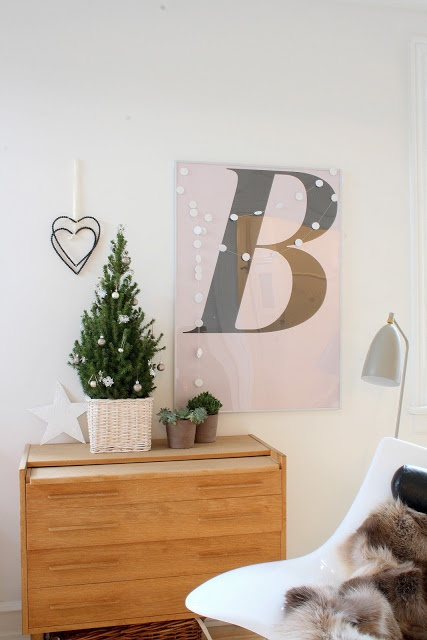 a mini tabletop Christmas tree with neutral ornaments in a neutral basket, a white paper garland for a minimal chic look