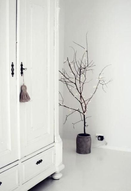 dried branches in a pot with lights are an amazing Christmas tree alternative for a minimalist space