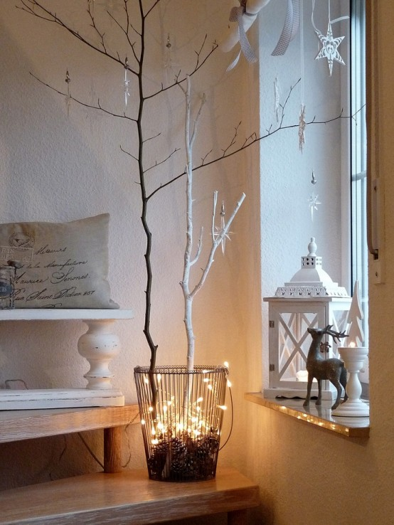 black and white branches, lights and pinecones in a wire basket and paper ornaments on all the branches
