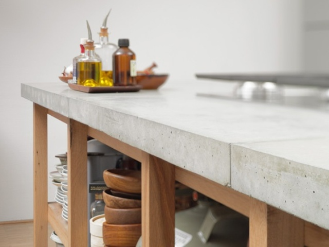 a wooden kitchen island with a concrete countertop looks modern and fresh and is very contrasting