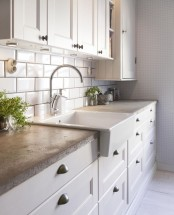 a white farmhouse kitchen with chic cabinets and concrete countertops plus potted greenery to refresh the space