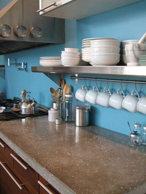 a blue kitchen with chocolate brown cabinets and a polished concrete countertop looks bold and catchy