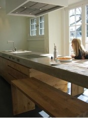 a minimalist kitchen with an oversized sleek wooden kitchen island and a concrete countertop plus wooden benches
