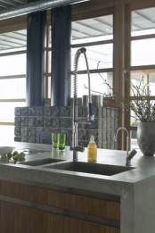 an industrial modern kitchen with wooden cabinets clad with concrete countertops looks super bold and very catchy