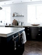 a Scandinavian kitchen with black cabinets, a white tile backsplash and concrete countertops looks ultra-modern and very fresh