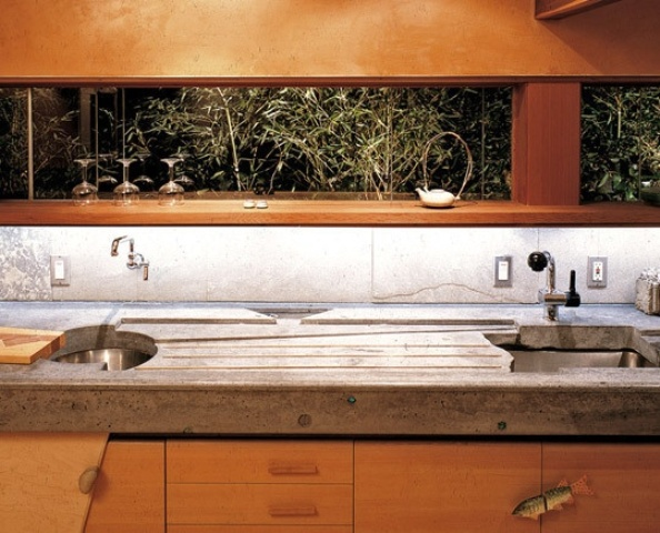 a peaceful kitchen of light colored wooden cabinets with a window backsplash and concrete countertops