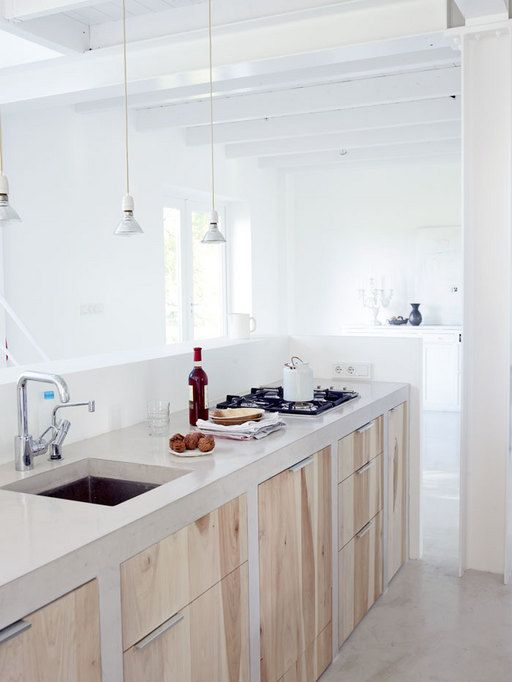 a minimalist light-filled kitchen with wooden cabinets and white concrete countertops plus pendant bulbs