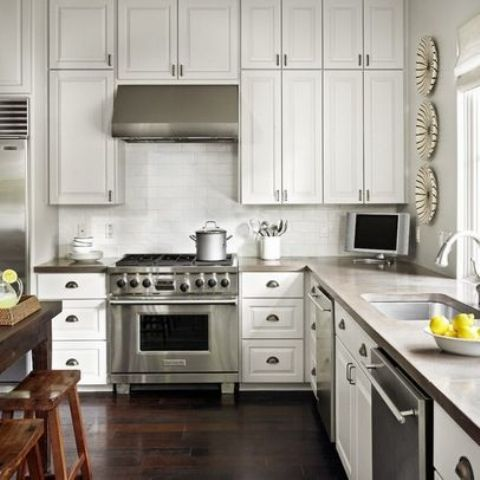 a simple white kitchen with concrete countertops, a white tile backsplash and lots of natural light incoming