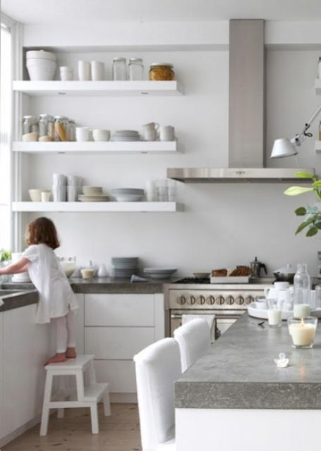 a white minimalist kitchen with concrete countertops and stainless steel appliances looks ultra-modern and very laconic