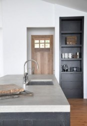 a minimalist monochromatic kitchen with white walls, black cabients and a black kitchen island with a concrete countertop
