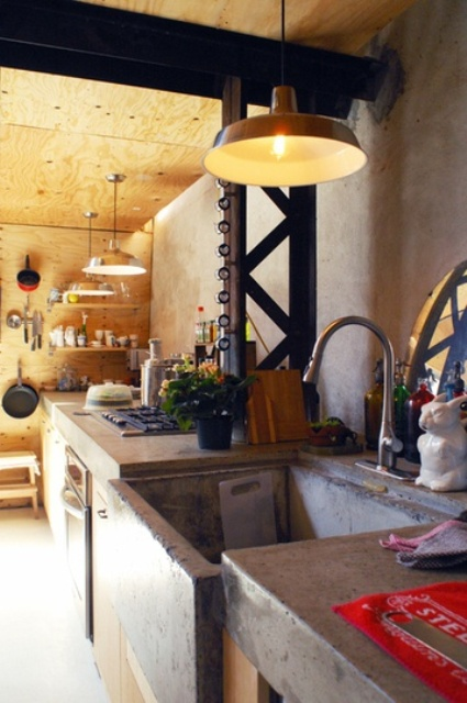 a rustic kitchen fully clad with light colored plywood and with concrete countertops and a sink for an industrial feel