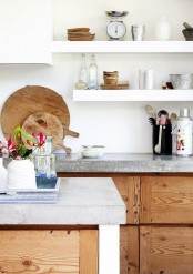 a modern kitchen with wooden cabinets, white walls and shelves and concrete countertops for an edgy touch