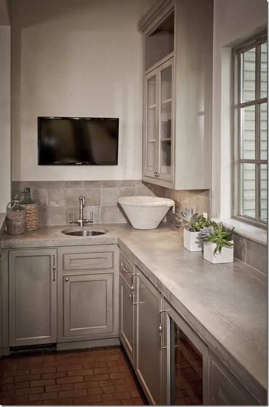 a grey farmhouse kitchen with cool cabinets and refined candles and concrete countertops plus tiles on the backsplash