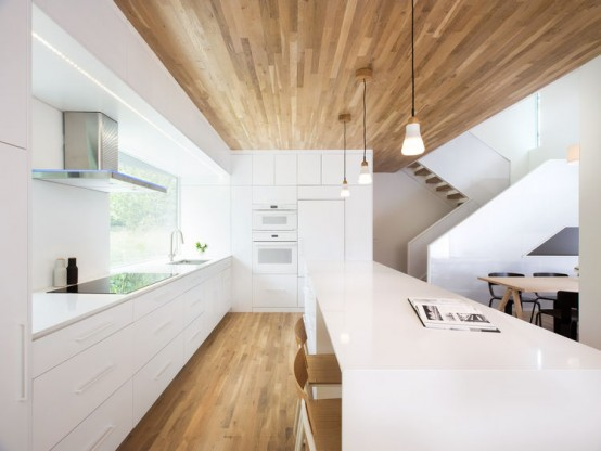 Minimalist home with oak surfaced interiors on a tricky for Minimalist homepage