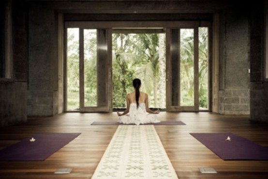 a contemporary meditation room with colorful rugs and a glazed wall for much light