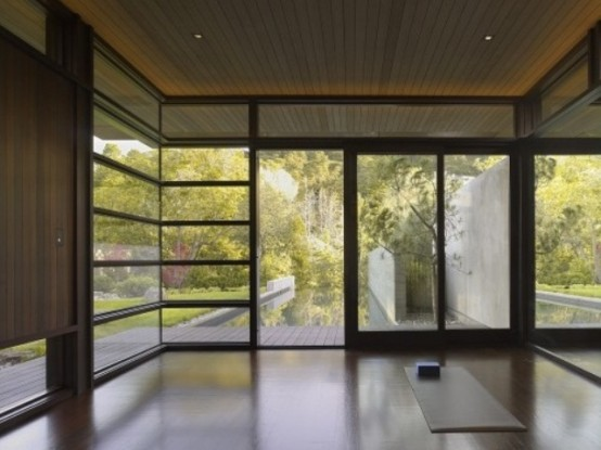 a minimalist meditation room with glazed walls for much light and air and just some rugs