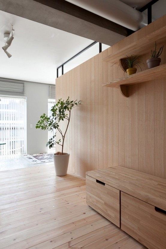 Modern Apartment Renovation With An L-Shaped Wooden Wall
