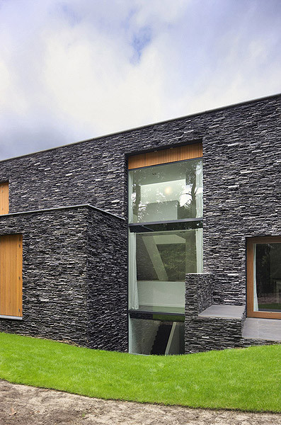 Modern forest house finished with stone bosvilla soest for Exterior stone design houses