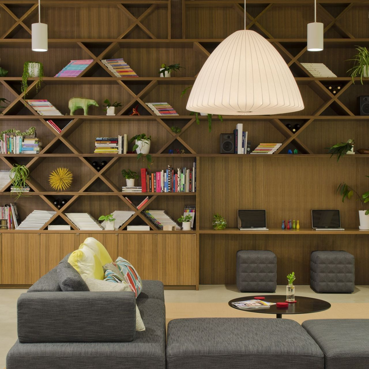 a modern home library with a shelving unit that takes the whole wall and some comfy sitting furniture