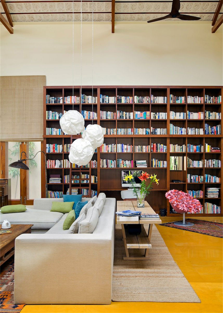 a large home library with an oversized bookshelf unit, modern furniture and shades on the windows