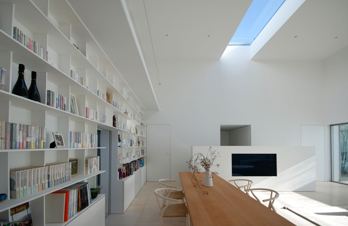 a modern and minimal home library with built in bookshelves and a large desk where you can read, skylights will give much light
